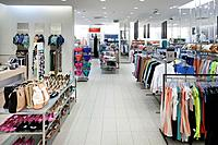 Fashion shop interior with display. Clothing and bags in retail store. Large aisle and elevated view.