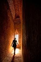 Silhouette of woman walking toward narrow window in a dark ancient temple.