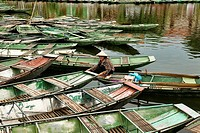 sightseeing boats docked on the Tam Coc River in Ninh Binh, Vietnam.