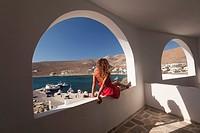 Woman sitting at the balcony, Folegandros, Cyclades Islands, Greek Islands, Greece, Europe.