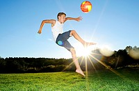 Young boy playing soccer on a meadow, Germany.