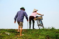 Vietnam, Ha Long bay on land, Ken Ga, karstic landscape around Hoa Lu, people on a dike.