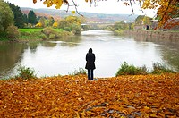 Autumn scene. Pensive woman at the river in Hannover Münden Germany.