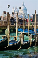 Gondolas, in the foreground and tourists in front of Salute Church, in the background, Venice, Italy.