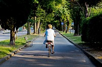 old woman cycling through the streets of Marghera, Italy