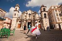 Santeria woman dancing in front of Cathedral of San Cristobal, Havana Vieja, Old Havana District, Havana, Cuba, West Indies, Central America.