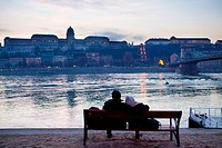 A couple rest in the shore of the Danube river, in front of the Royal Palace.