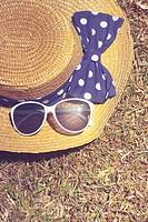 Pretty vintage straw hat with polkdot bow lying on dry Australian grass background. Travel outback australia.