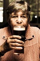 Dark photograph of an adorable senior woman enjoying a pint of cold dark beer inside bowls club. Social seniors.