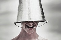 Funny photo of a smiling man laughing with ice bucket on head at an open-air concert. Summer music festivals.