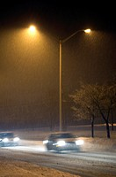 Snow falling on a deserted street at night in Toronto suburbs.