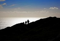 Silhouetted Hikers on Bear Island, County Cork, Ireland.
