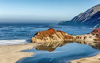 Rocky shoreline reflecting off of a pool of water. Little Sur River Beach, California, United States.