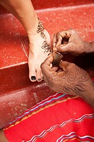Close-up shot of a local woman making a temporary tattoo, Stone Town, Unguja Island, Zanzibar Archipelago, Tanzania, East Africa.