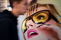 "Berlin. Germany. Graffiti in Hackesche Höfe entrance. A modern woman catching a man passing. Berlin ""the graffiti Mecca of the urban art world.† Whil..."