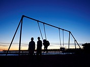 Silhouette of family at playground in front of pier, Cayucas, California, United States.