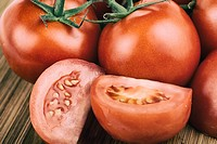 Tomatoes, Whole and Sliced, Chopped Vine Tomato on Cutting Board.