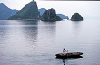 Woman rowing a boat in H? Long Halong BayUNESCO World Heritage Site Vietnam