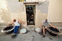 Fishermen preparing their fishing lines in the old town of Gallipoli, Puglia, Southern Italy.