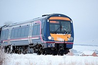 Local commuter train service running in winter scenery Montrose Scotland.