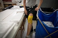 A runner in the physiotherapy room shows her knee after participating in a marathon. Madrid. Spain.