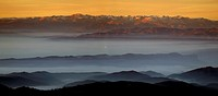 Pyrenees Mountain range and foggy Vic region valley seen from Turo del Home Peak at Montseny Natural Park in winter. Barcelona province, Catalonia, Sp...