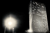 Night view of a modern architecture buildings with a lamppost in the foreground in the city of Tel Aviv, Israel