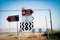 View of a several road signs indicating different places: Masada, Eilat and the first Potash Plant (1925-1948), with the Death sea on the background, ...