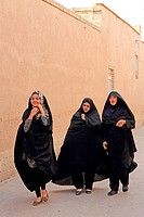 Three women walking along a street in the old town of Yazd, Iran, Asia.