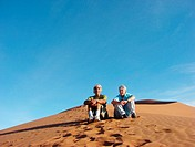 A couple sitting on a sand dune in Sossusvlei desert, Namibia