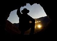 Man looking inside mine entrance, Mojave Desert, California, USA