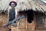 Banna tribesman holding a kalashnikov. He is standing in front of the hut where he is living. Omo valley ( Ethiopia).
