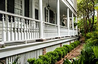 Historic home in Charleston South Carolina with side porches and a garden in the foreground.