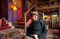 Caucasian man wearing a beret sits in Bohemian bar, W Oparach Absurdu pub, Praga district, Warsaw, Poland, Europe.