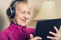 Woman wearing Bluetooth Wireless Headphone enjoying streaming media, content on her Tablet.