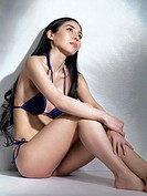 Beautiful Japanese woman sitting on the floor in bikini in artistic dramatic light.