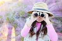 A young girl pretending to be on safari looking through binoculars.