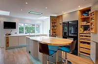 A modern kitchen inside a home in the UK with the doors open on the food cupboards.