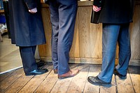 Closeup of legs of three unrecognizable men on the cue of a coffee shop in London, England, UK, Europe