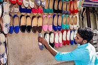 India, Asian, Mumbai, Apollo Bandar, Colaba, Indumati Sakharkar Marg, Causeway, Market, shopping, man, sidewalk vendor, woman´s, shoes, setting up sho...