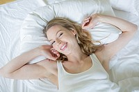 Pretty blonde woman waking up and stretching in bed smiling at camera