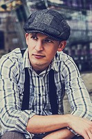 Cross processed portrait of a retro 1930s man wearing hip men´s fashion with hat sitting in city backstreets.