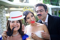 Just married couple playing with costumes and guests in wedding party.