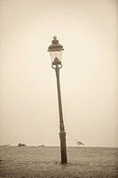 Empty waterfront in heavy fog. Tranquil city scene with old lamppost in Stockholm, Sweden.