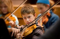 boy playing viola in orchestra.