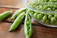 Peapods and glass bowl full of peas.
