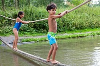 Children dressed in swimming suits balancing on a rope above water.