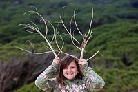 girl with wooden horns imitating deer antlers with a twig. Cadiz, Andalusia, Spain, Europe