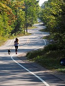 Wisconsin Door County Elison Bay Windy Road with female runner and dog.