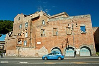 Police car passing by a building at Via dei Fori Imperiali in Rome, Italy